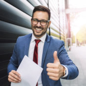 Handsome young smiling businessman giving thumbs up